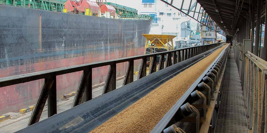 Banda transportadora con granel y un buque al fondo