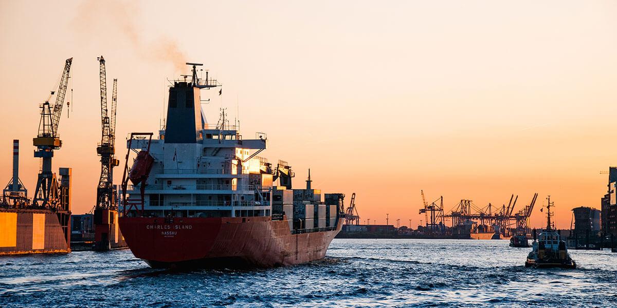Buque en el oceáno entrando a un puerto con grúas