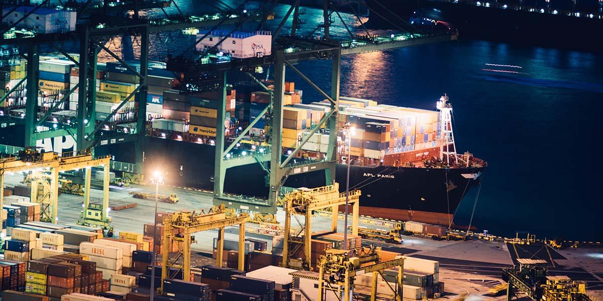 Contenedores apilados, grúas y un buque atracado en un puerto