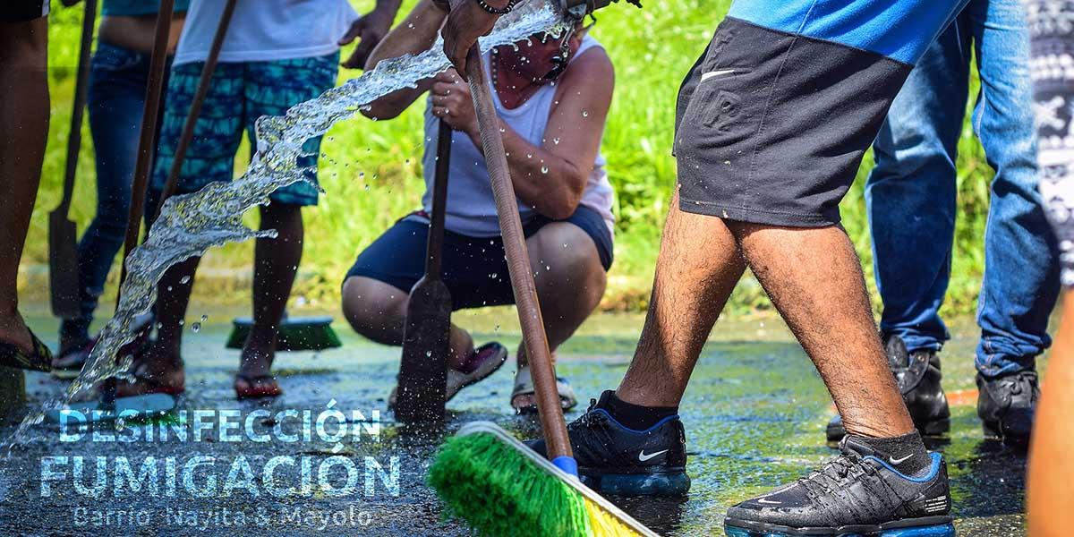 Personas limpiando con escobas y agua que sale de una manguera