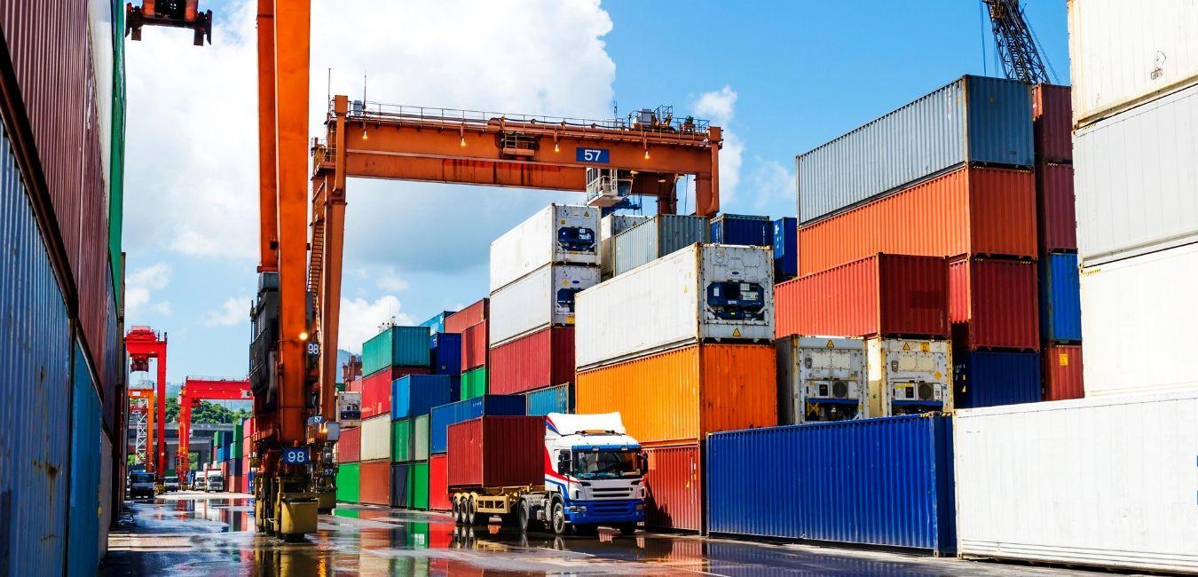 Contenedores apilados con grúa y camión en terminal portuaria
