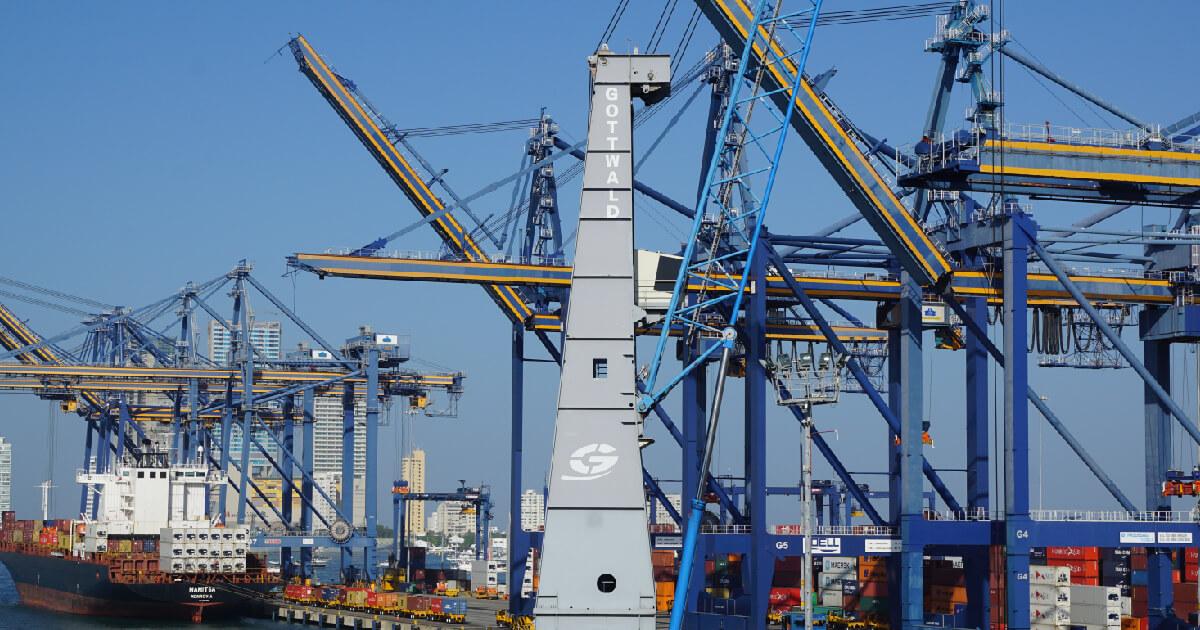 Contenedores, barcos y grúas en puerto marítimo