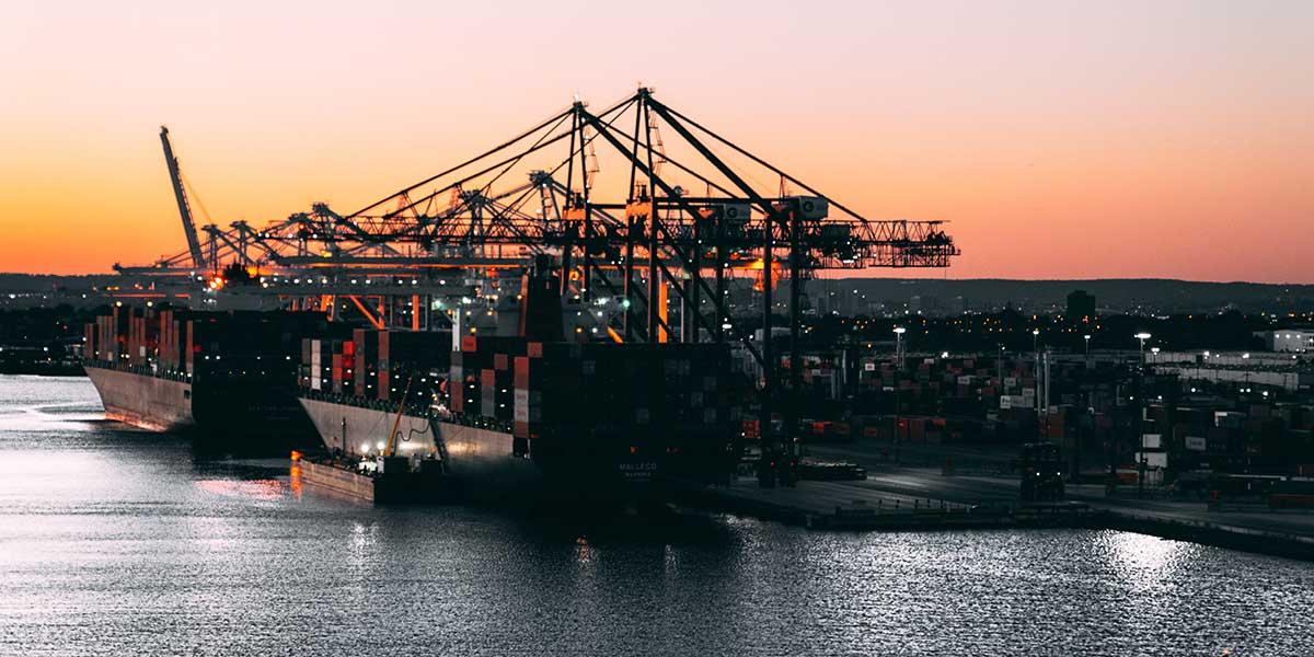 Vista aérea de un puerto marítimo con buques, grúas y contenedores